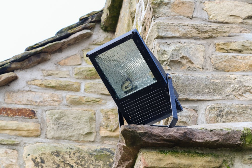 Photo home security light outdoor on the corner of a stone cottage metal halide floodlight enclosure