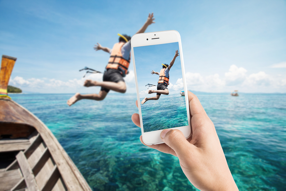 Photo taking photo of snorkeling divers jump in the water