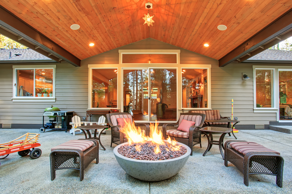 Photo large back yard with grass and covered patio with fire pit