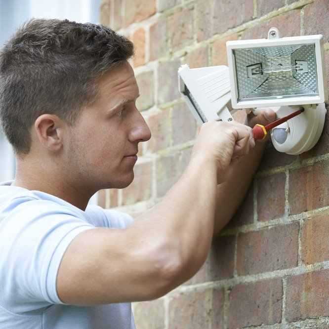 Photo security consultant fitting security light to house wall