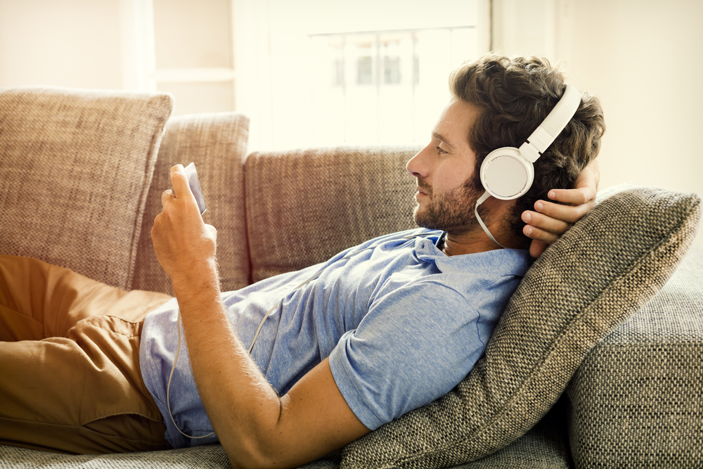 Photo man on couch watches a movie on mobile phone