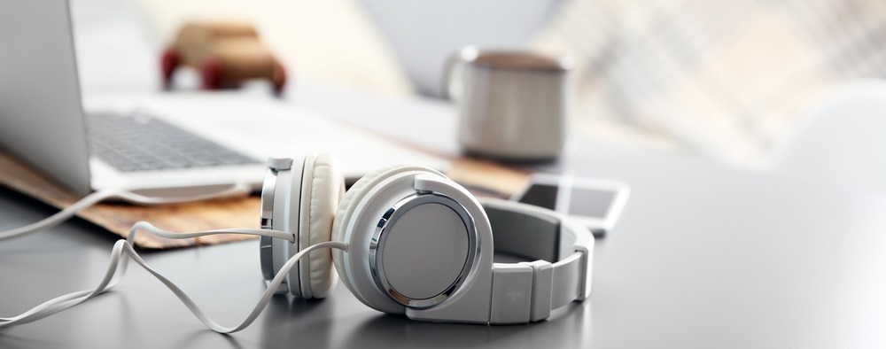 Photo headphones phone and laptop on white table against defocused background