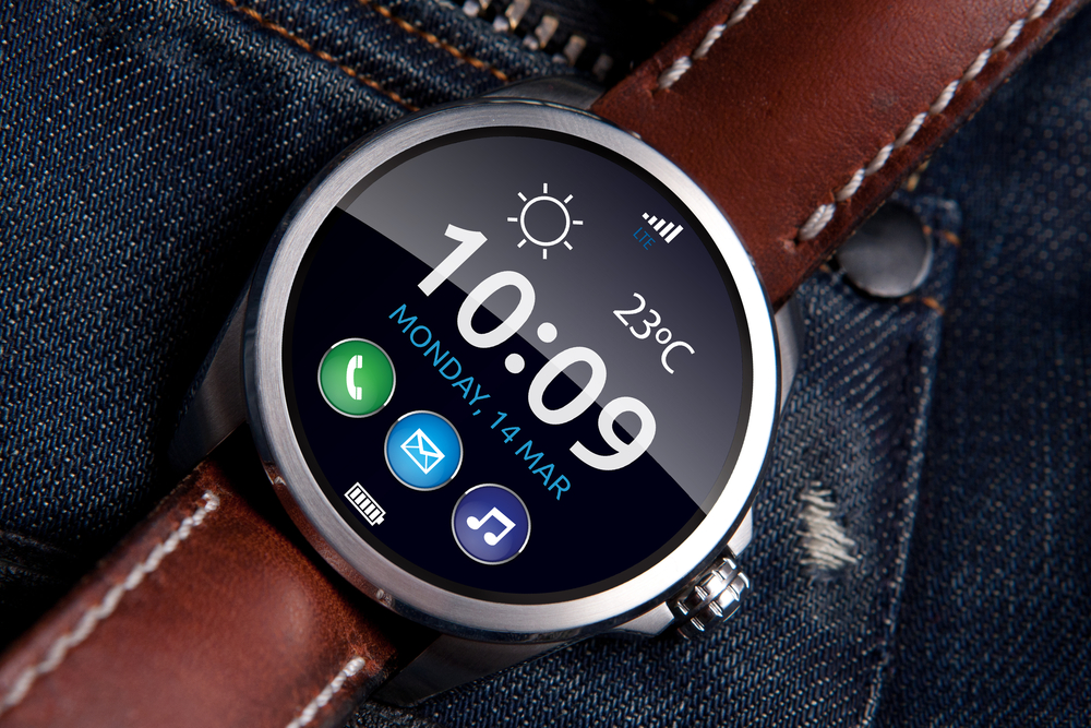 Photo smart watch concept on matte and polished metal case with brown leather strap on blue jeans