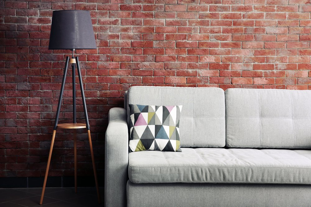 Photo grey sofa and floor lamp against brick wall in the room