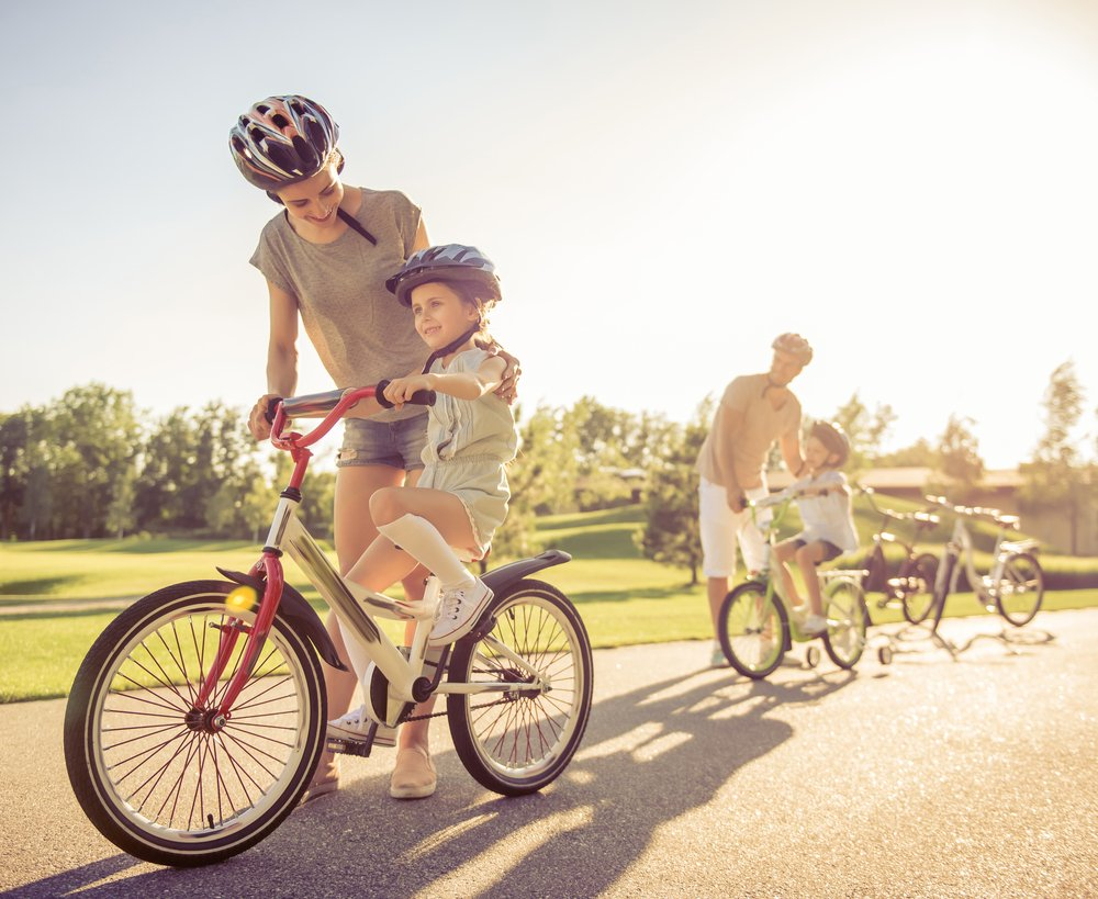 Photo happy family is riding bikes outdoors and smiling parents are teaching their children