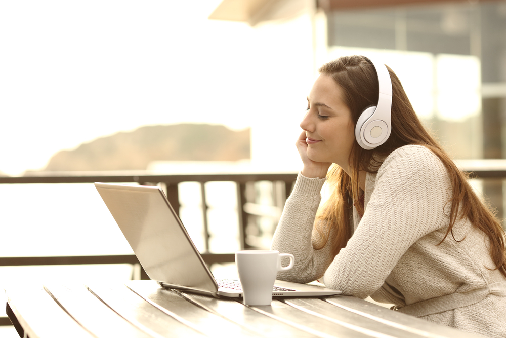 Photo girl with eyes closed listening music with a laptop and headphones and relaxing in an hotel terrace