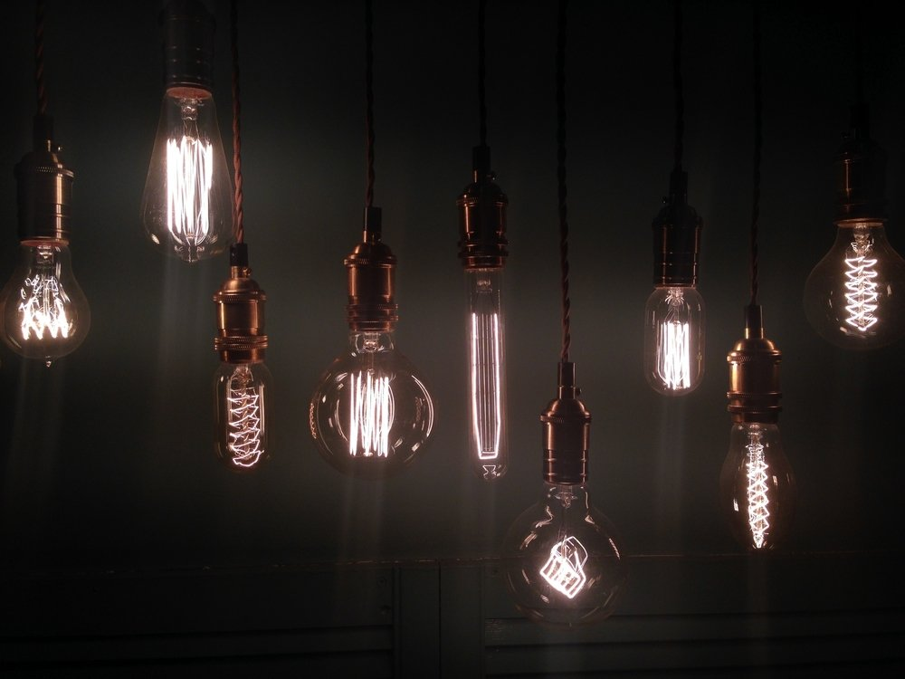 Photo various lit light bulbs hanging against sky at night