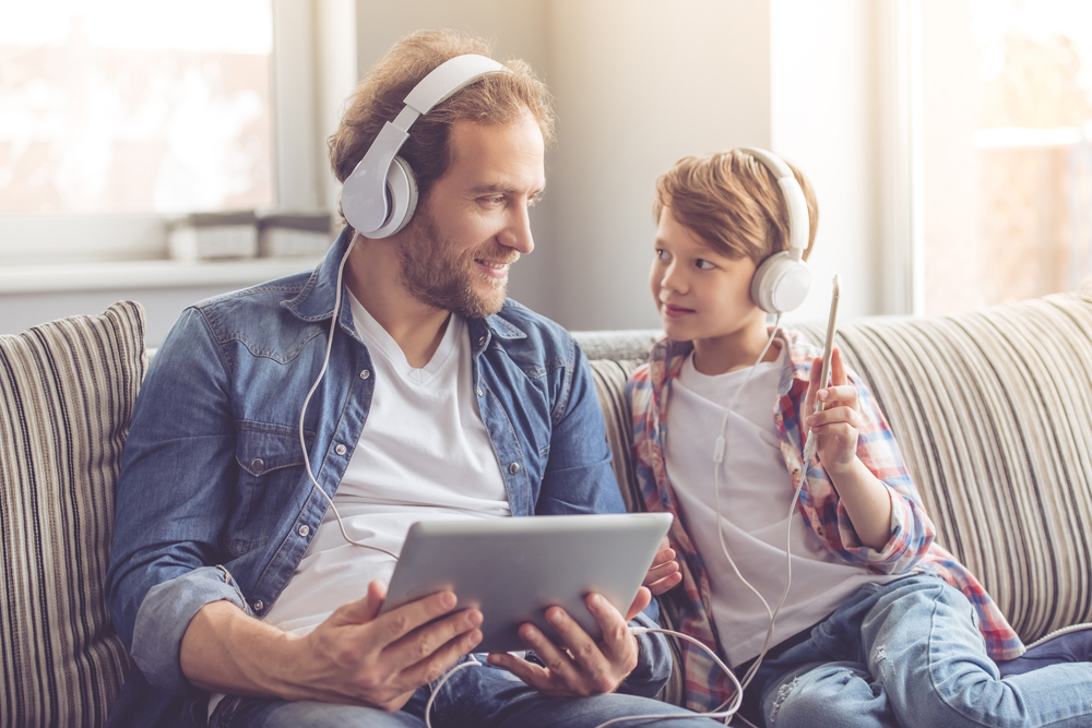 Photo father and son in headphones are listening to music using gadgets and smiling while spending time