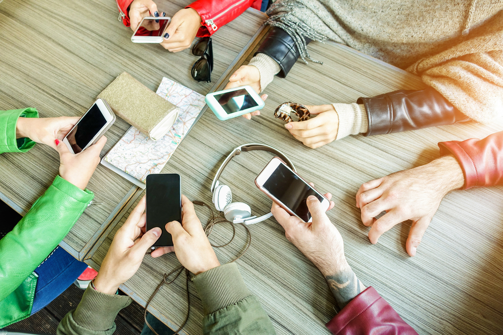 Photo group of friends are addicted using mobile phone devices upper point of view people hands using