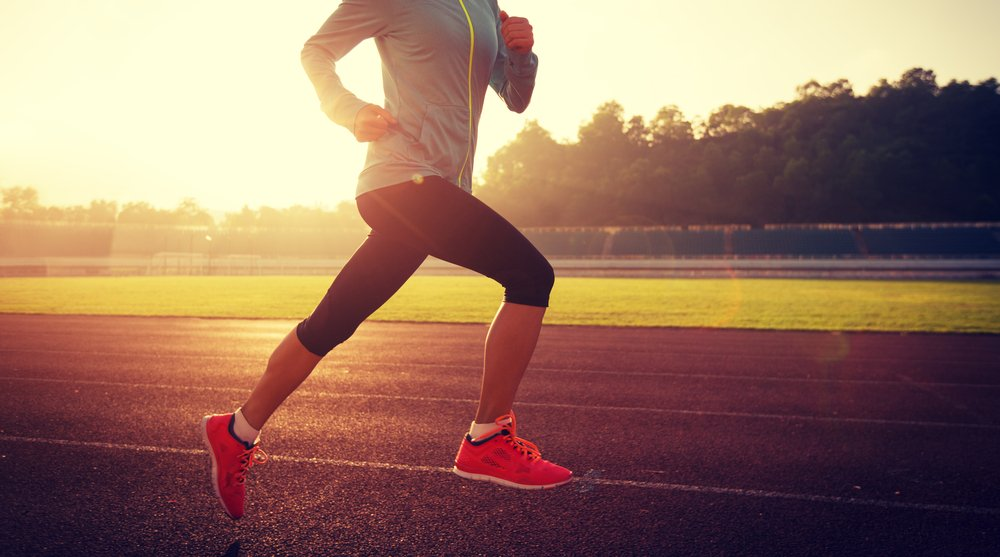 Photo young woman running during sunny morning on stadium track