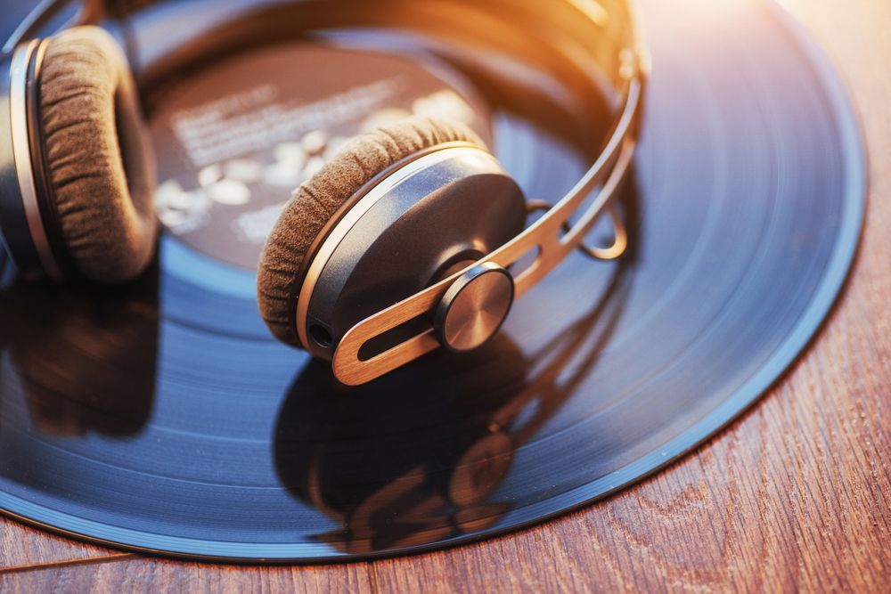 Photo vinyl record and headphone over wooden table