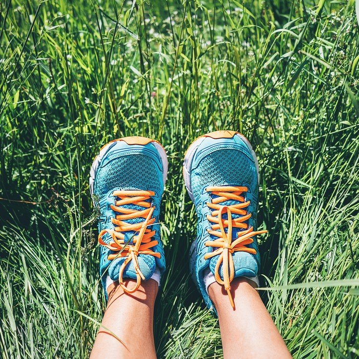 Photo woman feet in bright blue running shoes are in high green grass