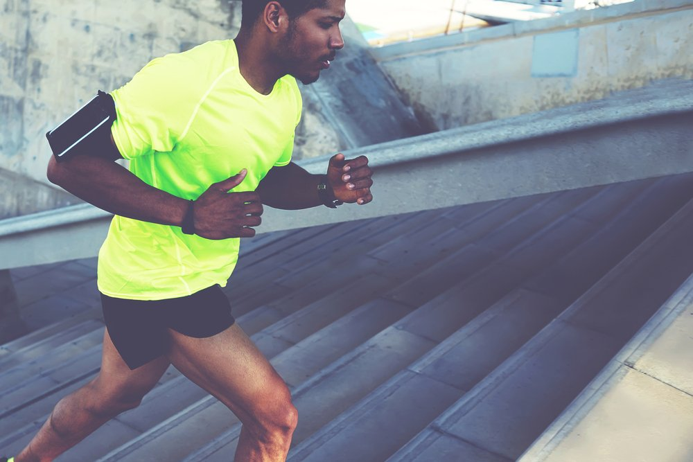 Photo cropped shot male dark skinned athlete running up a flight of stairs with speed sporty young man