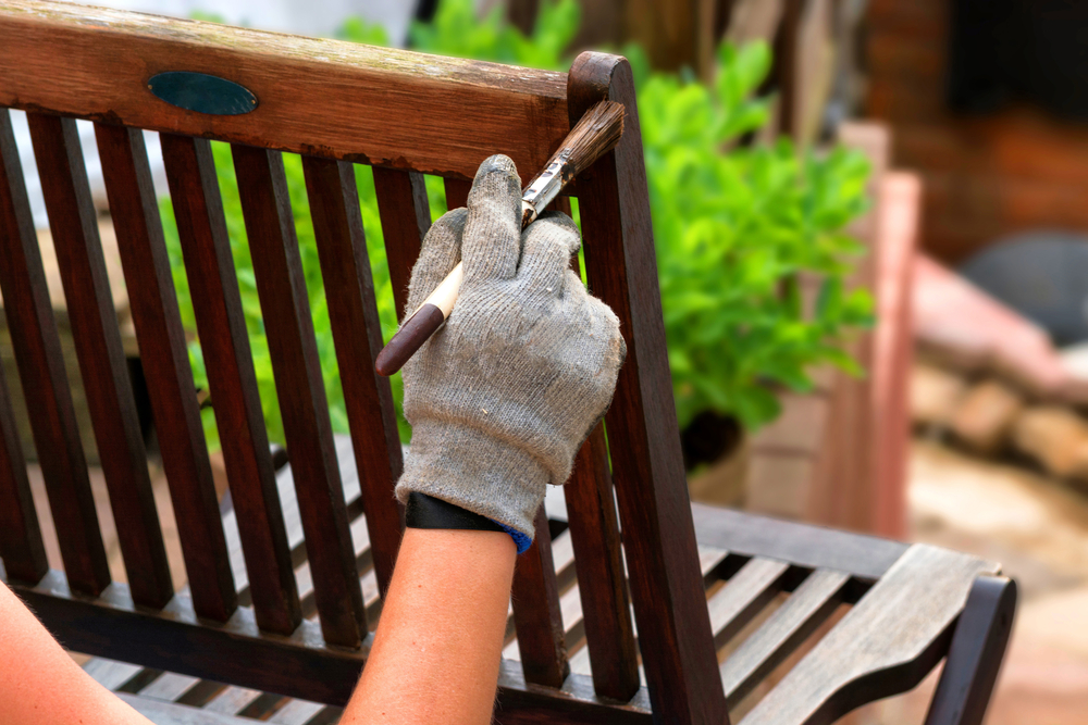 Photo painting and applying protective varnish on a wooden garden chair