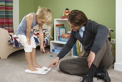 Father assisting child using scales