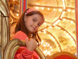 Picture shows a child seated on a fairground carousel.