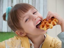Picture of a young girl eating a waffle with a cheeky look on her face.