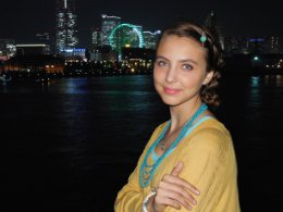 Picture of a young woman standing on the waterfront at night with the Yokohama cityscape in the background.