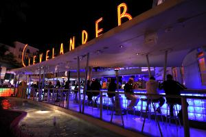 Picture shows an outdoor Miami bar scene in the evening illuminated with neon lights.