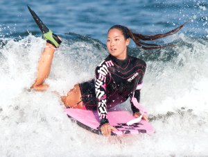 Picture shows a shot of a woman body-boarding in the surf.