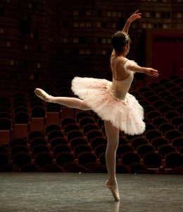 Picture shows a ballerina dancing on stage in a low-lit theatre.