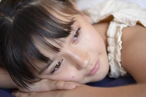 Portrait of a young girl resting her head on her hands as if about to sleep.