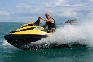 Picture shows a man riding a jet-ski, passing the camera at high speed.