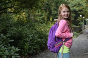 Picture shows a young girl, wearing brightly coloured clothes and a backpack, on a gravel track leading to a bridge in woodland, looking back towards the camera.