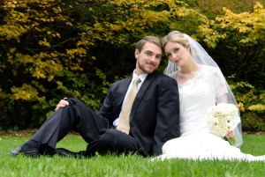 Picture shows a man wearing a suit and a woman wearing a wedding dress, sitting on grass with a background of yellow-leaved bushes.