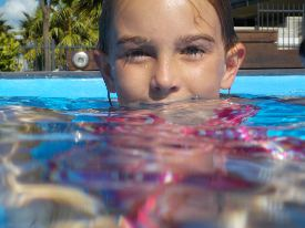 Picture shows a young girl standing in a swimming pool.