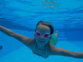 Picture of a young girl swimming underwater, demonstrating the underwater capabilities of the camera.