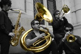 Picture of four street musicians with brass instruments. The image is monochrome except for the instruments, demonstrating the camera's Selective Colour feature.