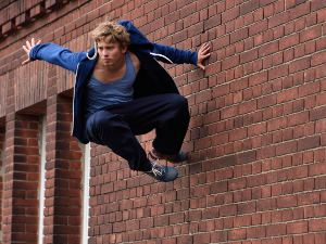 Picture of a male parkour practitioner bouncing off a red brick wall high up.