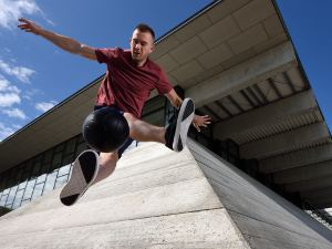 Picture of a footballer in mid-air in an urban space shot from a low angle.