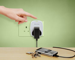 F7C009 Conserve Socket Energy Saving Outlet with a cellphone