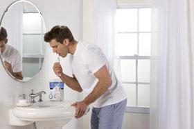 Waterpik WP-100 Ultra Water Flosser in use by a man in a bathroom