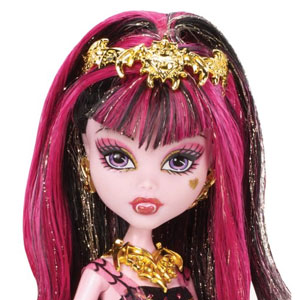 Draculaura wears spooktacular makeup and her hair is styled with gold detailing and pink streaks