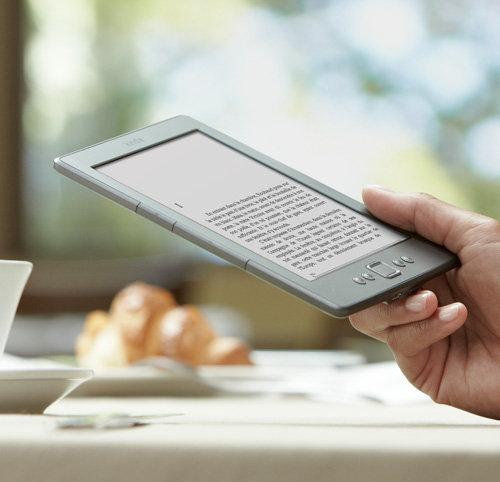 Liseuse Kindle : appareil tenu en main, lecture dans un caf�