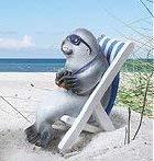 Witzige Robbe als Urlauber auf einem Liegestuhl blau