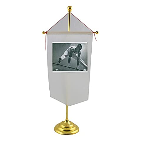 Table flag with A male athlete jumping above a horizontal bar in a 1938 German documentary filmm