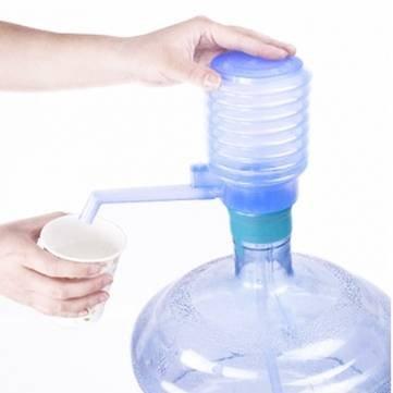 Acqua potabile in bottiglia pressa della mano dell