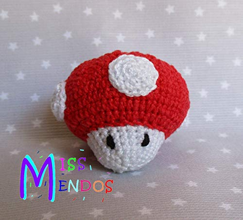 """Llavero amigurumi inspirado en la conocida """"seta"""" o champiñón de los juegos de Super Mario. Tejida a mano con la técnica amigurumi, y con ojos bordados a mano."""