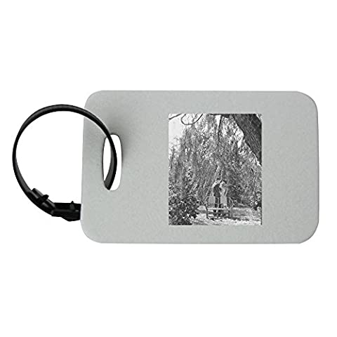 Luggage tag with Man and woman are about to kiss underneath tree. people, man, woman, garden, chairs, standing, kiss, relationship, romance, love, heteroseksual couple, tree,