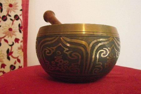 Tibetan Singing Bowl; with attractive Grey-Black Coating on Outer/Inner Surface; Engraved with 'Om Mani Padme' Symbols on Outer & Inner Surfaces; 5.5in Diameter; 700grams weight. Plays a lovely clear note. Playing Stick Included by Spiritual Gifts