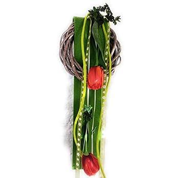 Weidenkranz mit leuchtenden Tulpen, hängend fertig als Geschenk verpackt