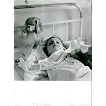 Vintage Foto de un Kid tumbado sobre un cama de hospital.