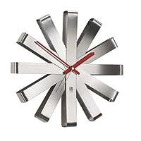 Wall Display Ribbon: un orologio da parete purista e ricco di stile con lancette rosse e argento realizzato con metallo spazzolato. Grazie alla forma a stella il quadrante non à necessario: ogni punta corrisponde ad un'ora. In questo modo leg...