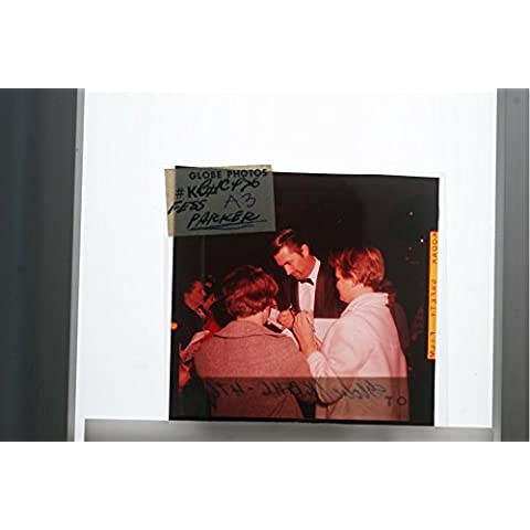 Slides photo of Fess Parker signing autographs from his fans.