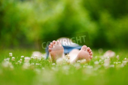 "Poster-Bild 110 x 70 cm: ""Childrens feet on grass outdoors in summer park"", Bild auf Poster"
