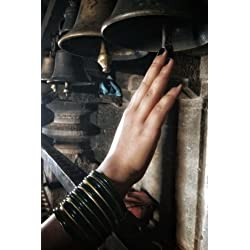Woman Wearing Black & Gold Bangles Ringing a Vintage Bell Journal